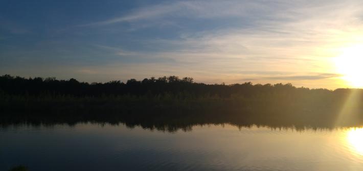 Das Bild zeigt einen Teil eines Flusses und im Hintergrund geht gerade die Sonne unter.
