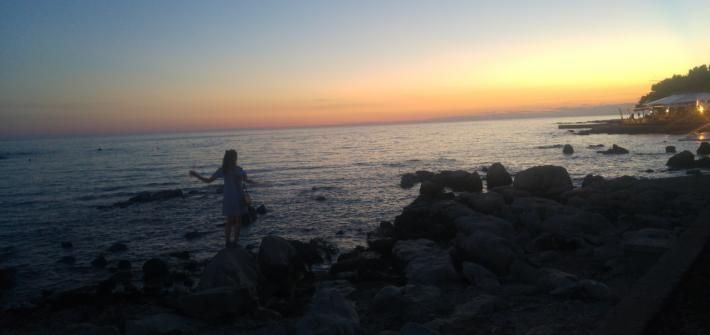Autorin auf einem Felsen am Meer in Umag. Im Hintergrund geht gerade die Sonne unter und der Himmel leuchtet in waren gelb-orange.