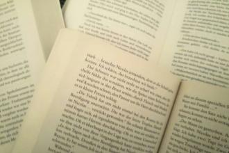 Mehrere aufgeschlagene Bücher übereinander. Sie sollen als Beispiel für die gelesenen und bewerteten Bücher stehen. Der Text handelt von Buch-Bewertungen.