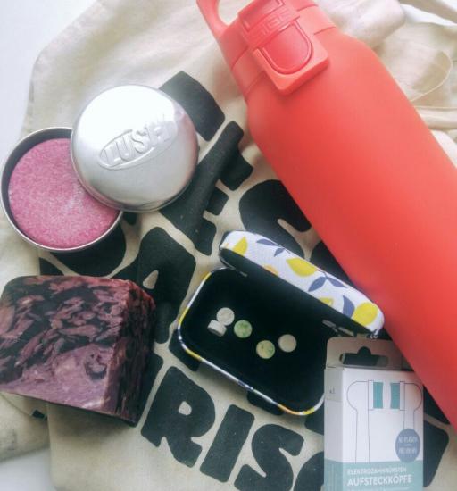 FlatLay einer Trinkflasche, eines Stoffbeutels und mehreren verpackungsfreien Kosmetikartikeln. Meine persönliche vegane Reise.