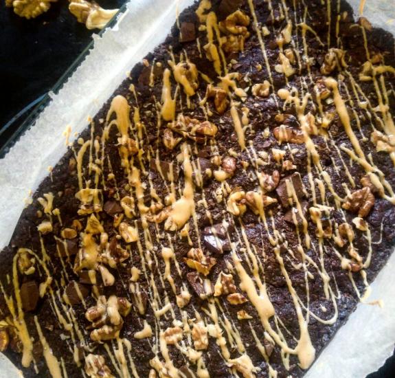 Eine Form mit veganen Brownies. Die Brownies sind mit Walnüssen und Erdnussbutter verziert.