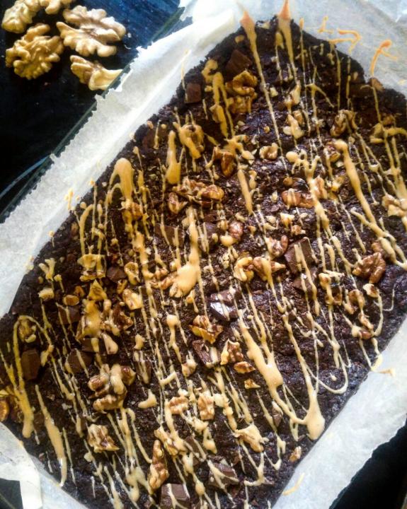 Form mit veganen Brownies, die mit Walnüssen und Erdnussbutter dekoriert wurden.