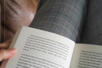 Buch das am Oberschenkel aufliegt und gerade gelesen wird. Text handelt von einer Buch-Bewertung.