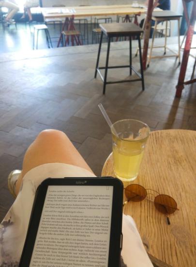 Ein E-Reader auf einem Oberschenkel mit einem offenen Buch. Daneben ein kleiner Tisch mit einem Glas Eistee und einer Sonnenbrille.