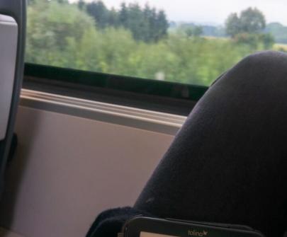 E-Reader auf einem Oberschenkel auf dem ein Buch geöffnet ist. Im Hintergrund ist ein Zugfenster mit vorbeiziehender Landschaft zu erkennen.