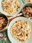 Zwei Teller mit Spaghetti in Eierschwammerl-Soße mit zwei Salatschüsseln.